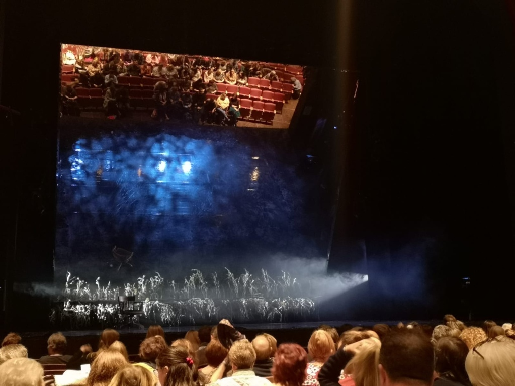 A photo taken of the stage before The Lovely Bones started. Audience members can be seen at the bottom of the photo but can also be seen at the top of the stage as they are reflected in the mirror.