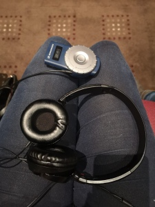 A photo taken looking on to Lucy's lap. She is wearing blue jeans. The headphones and audio description box are laying on her lap.