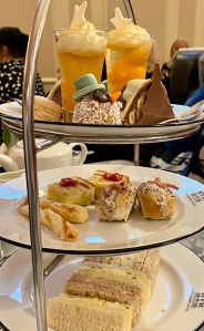 Afternoon tea cake stand. On the bottom are finger sandwiches, in the middle is a mini roll, mini toastie, and mini cheese straw. On the top is a selection of cakes including a shot glass with trifle in and a snowman head covered in coconut.