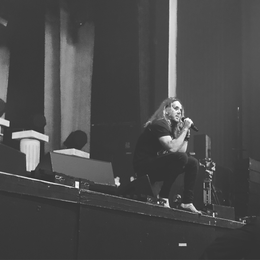 A black and white photo of Tim Minchin sitting at the edge of the stage with a microphone in his hand pointing towards his mouth.