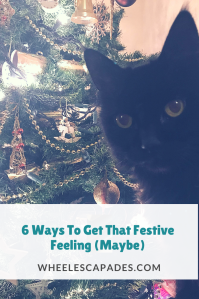 An image to pin. Title text 6 Ways To Get That Festive Feeling is placed over the photo of fluffy cat photobombing the Christmas tree.