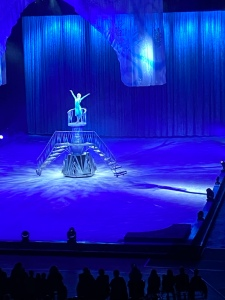 Elsa is standing on a high metal platform with stairs in the centre of the ice rink. She is singing with her arms stretched upwards.