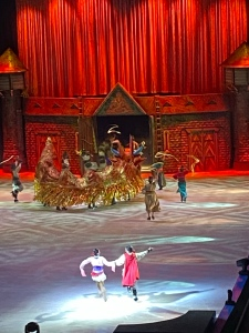 Mulan is on stage skating with a giant dragon made from multiple people. There is a red curtain backdrop.
