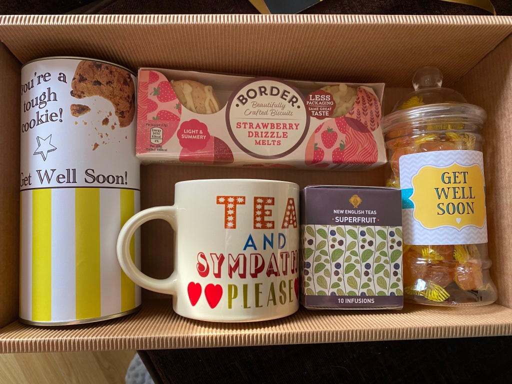 A view inside the hamper. There is a jar of boiled sweets saying get well soon, a mug saying tea and sympathy please, a purple box of super fruit tea, strawberry flavour Boarders biscuits, and a tin of chocolate chip cookies saying you're a tough cookie.