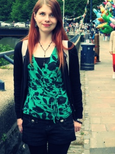 A photo of Caz standing in the street by a river. She has red hair, a green and black top, black cardigan, denim shorts and thick black tights. You can not tell Caz has any disability.
