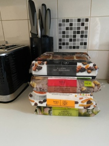 A pile of hot cross buns on my kitchen side in packets. The flavours are, luxury fruit, chilli and cheese, orange marmalade, and apple. The kitchen counter is white, the tiles and black and white, plus you can see a black toaster and knife block.