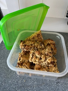 A plastic container with homemade flapjacks in. There are sultanas in the bakes. The container has a green lid which is open and propped to the side.
