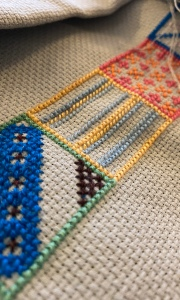 A close up of my cross stitch project. Geometric shapes stitched in bright colours.