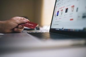A sideways shot of a laptop obviously displaying online shopping. To the left is a hand holding a bank card at the ready.
