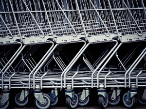 A close up black and white photo of stacked up shopping trolleys empty waiting for use.