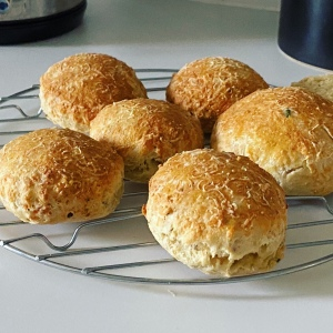 Six golden looking cheese scones that haven't risen very much. They are on a cooling rack on a white kitchen surface.