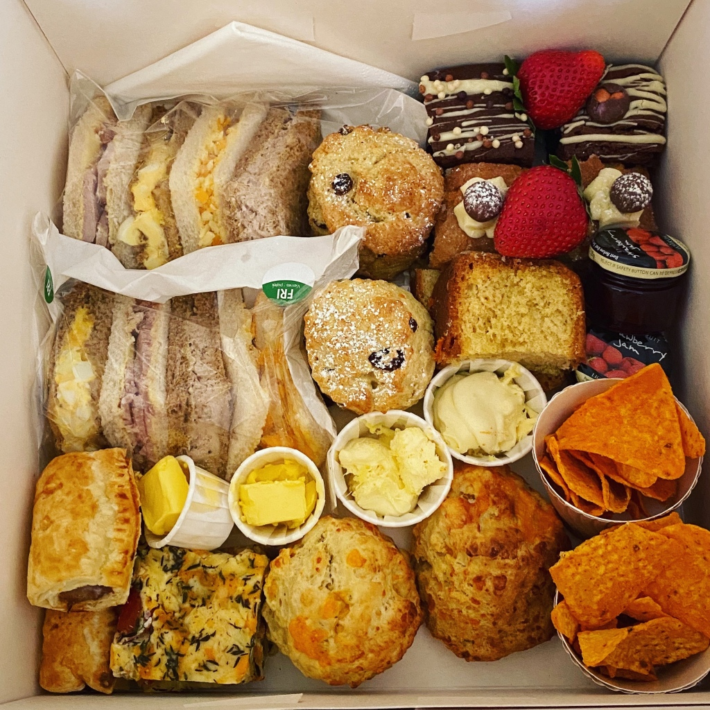 A white cardboard cake box filled with all the afternoon tea treats listed below in the post.