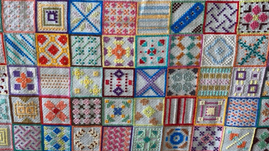 This photo is taken at a distance from the cross stitch fabric. All the squares are in rows of 10 each one touching the next. Like a grid filled with patterns. A variety of every colour is used and each design is different.