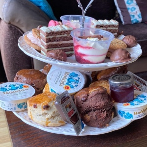 A side on photo of the two tiered cake stand with all sweet items on. The cakes mentioned above, along with chocolate truffles and chocolate scones.