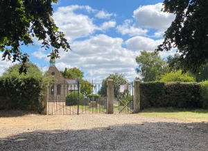 Iron gates lead into the graveyard with trees either side. The chapel is the the left and the sky is blue and sunny with white clouds.