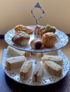 A two tiered cake stand with finger sandwiches on the bottom, and savoury bites on the top. Including a roll, a biscuit, a sausage roll and a muffin.