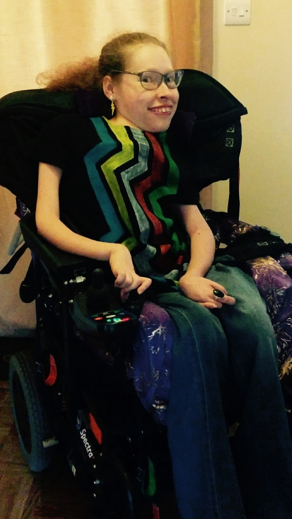A photo of Fleur sitting it her wheelchair. She has long curly blonde hair in a ponytail. She is wearing a black top with rainbow coloured strips in the Disability Pride logo. She is smiling and wearing glasses.
