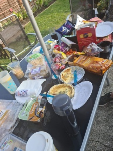 A black glass garden table with parasol pole is scattered with paper plates and packets of food including sausage rolls, quiche and cups of drink.