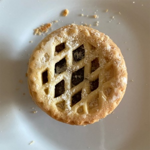 Photo taking looking down onto a mince pie with a lattice top. It is on a white plate.