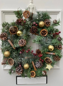 The second wreath is hanging on a white door. There is a letter box at the bottom. The wreath is green with gold baubles, cinnamon sticks, orange slices, pine cone and red berries.