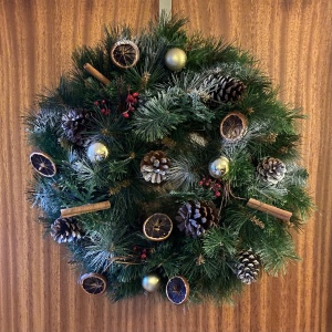 The wreath I constructed is hanging on a wooden door. The wreath is decorated with pine cones, cinnamon sticks, gold baubles and red berries. It has touches of white snow spray on.