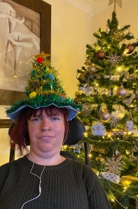 A phot of me from the shoulder up, I am beside a Christmas tree that has gold decorations and lights twinkling. I have a Christmas tree shaped hat on that is made of green tinsel and coloured Pom poms.