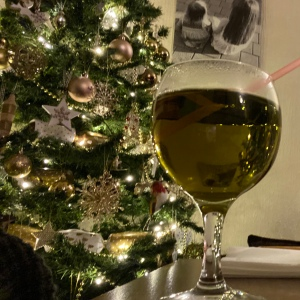 A wine glass filled with pale green liquid is on the corner of a table by a Christmas tree with lights and gold decorations.