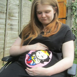 Ami is sitting in her wheelchair, she has long brown hair and is wearing a black t shirt with a baby superhero on the front. Ami has a bump and looks pregnant.