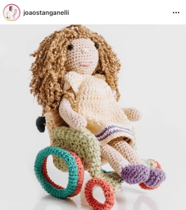 A crochet doll with brown curly hair in a crocheted green and orange wheelchair.