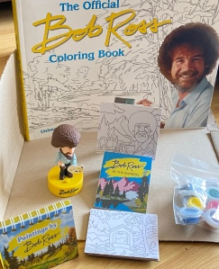 Bob Ross figure, paints and colouring book.