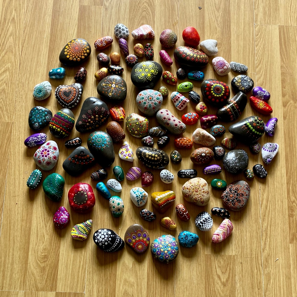 All 100+ stones arranged in a circle shape on a wooden floor.