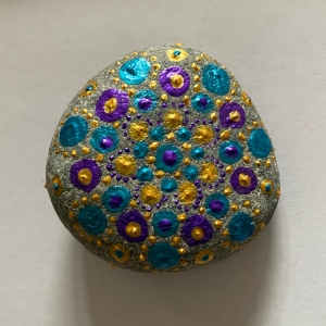 Round grey stone painted in dots of blue, gold and purple in a mandala design.