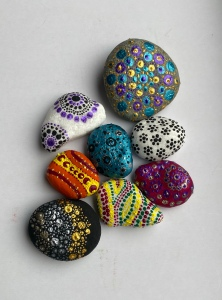A collection of eight painted stones on a white background. Included is a white somber with purple and black mandala pattern, a matte black stone with clusters of various sized dots in gold, silver and bronze, and a purple stone with a floral design.