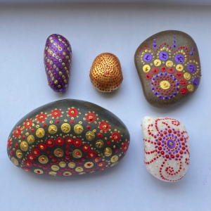 Fine boldly designed stones on a white background. Including A long cylinder stone painted metallic purple. It has alternating rows of gold and red dots spiralling g around the stone. And Large dark grey semicircle shaped stone with a half mandala design in red and gold dots.