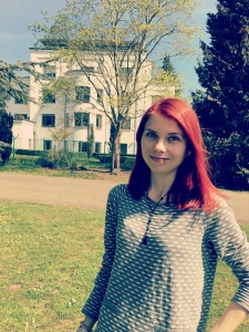 A photo of Caz from the waist up. She is standing and wearing a grey top. She has long red hair that is being slightly blown by the wind. In the background are trees, a large white building and blue sky.
