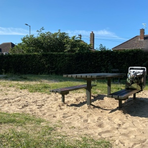 A wooden picnic table with bench seats either side is in the middle of a sand area which is then surrounded by grass. The sky is clear and blue.